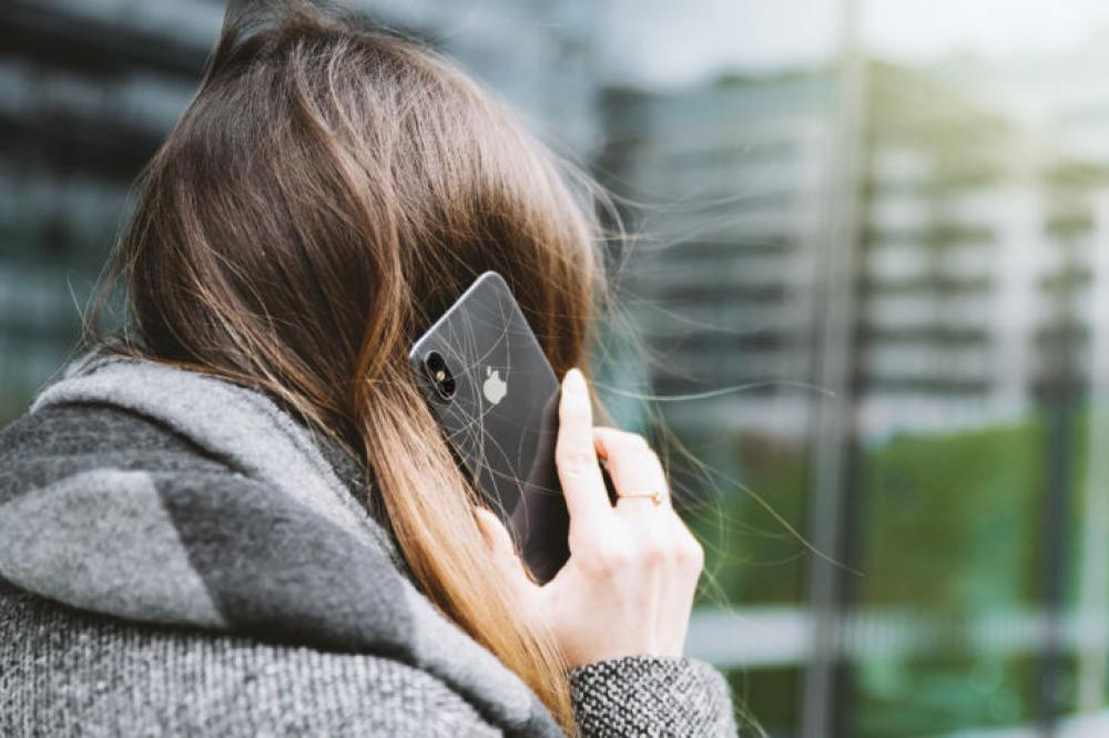Woman talking on cell phone, back view | Image Finder