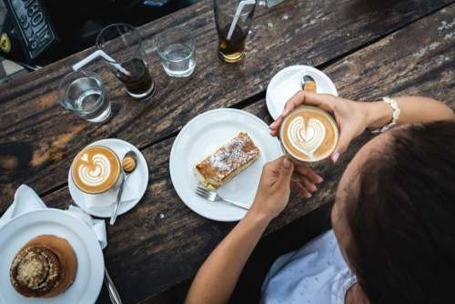 Girl treating herself with flatwhite coffee and cake