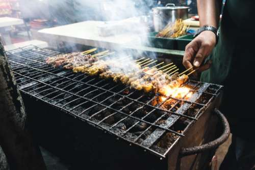 Grilling chicken satay
