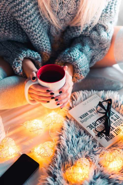 Woman in a winter mood with hot tea and a book