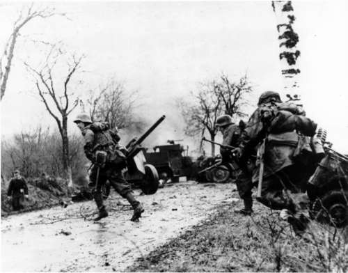 German troops advancing past abandoned American equipment during the Battle of the Bulge free photo