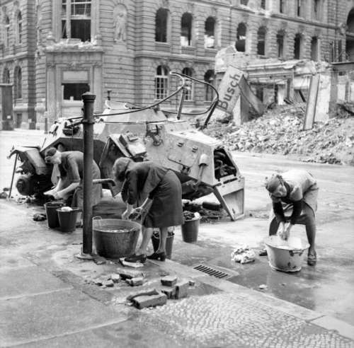 German women washing clothes at a cold water hydrant in a Berlin street, World War II free photo
