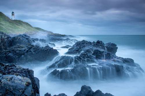 Lighthouse, rocks, waves, and ocean on a stormy day free photo