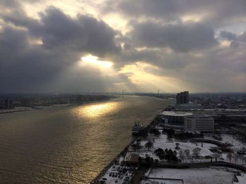 Sun shining through the clouds on the river in Detroit, Michigan free photo
