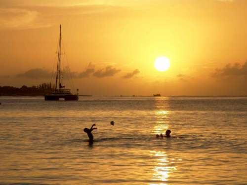 Sunset over the ocean with two people playing in Jamaica free photo