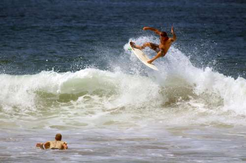 Two surfers riding waves in the ocean free photo