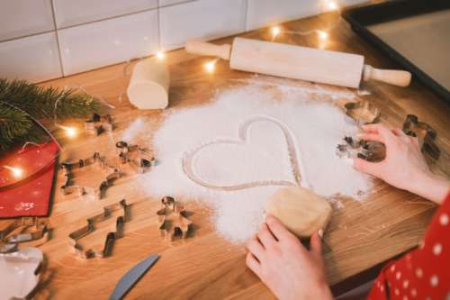 Woman bakes cookies. Symbol of heart in flour on a wooden table in the kitchen