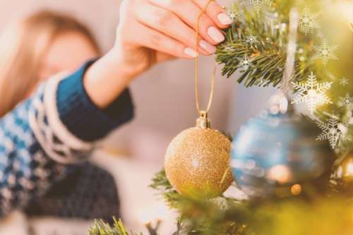 Woman decorating Christmas tree with baubles