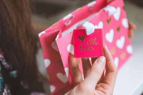 Valentine's Day, Woman received a gift in a pink small bag from love