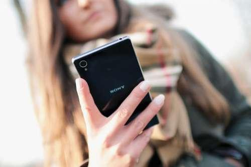 Back black luxury smartphone in hand modern woman