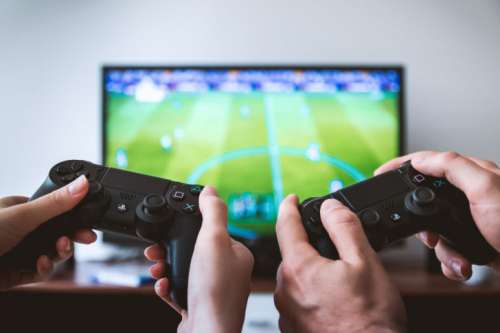 Hands holding the game controller while playing game on TV