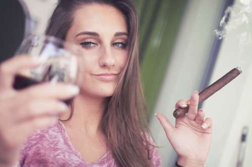Young girl with a cigar and a glass of alcohol