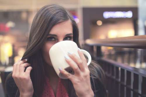 Portrait of young girls while drinking coffee in a shopping center