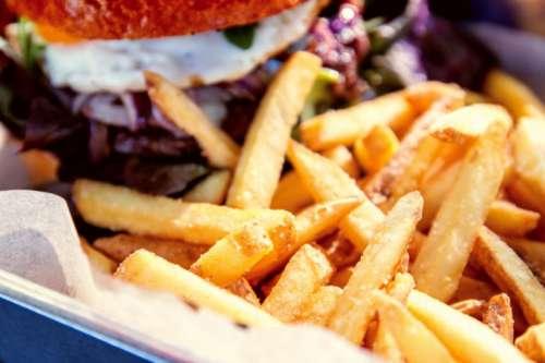 Detail of fries with hamburger at restaurant