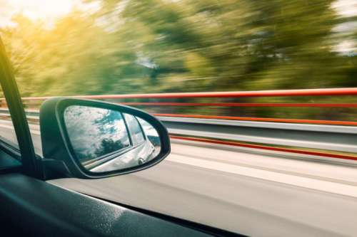 The reflection in the rear-view mirror of car in motion