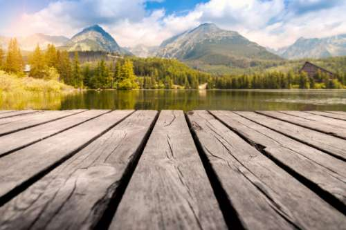 Majestic mountain lake in National Park High Tatra. Wooden table place of free space.