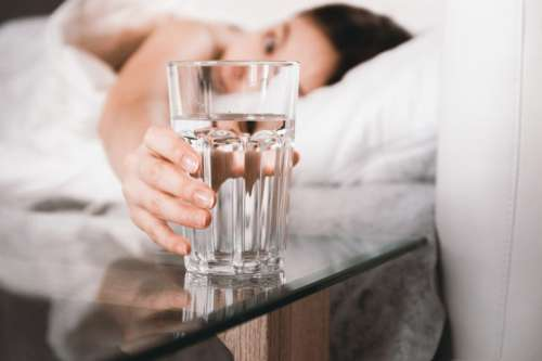 Close up Woman holding glass of water on bed in the morning