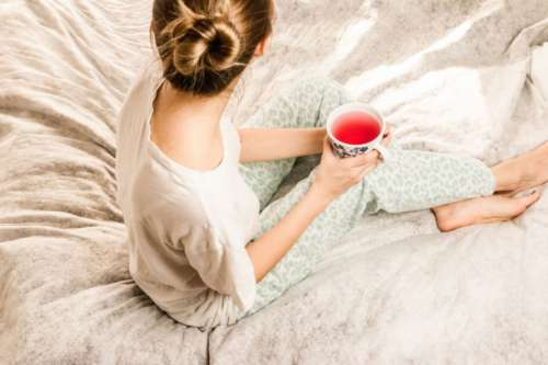 Attractive young girl in a pajamas holding a cup of tea while sitting in white bedding