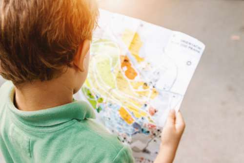 Small boy looking in to the map at amusement park