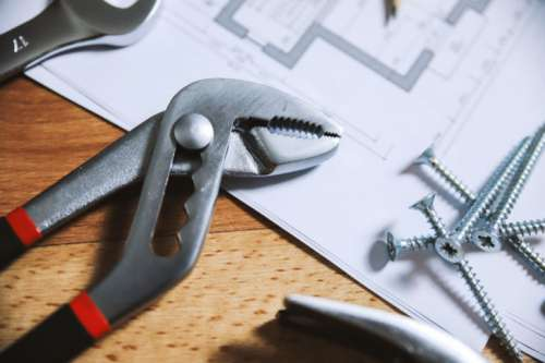 Pliers and nails on a wooden floor with house plans