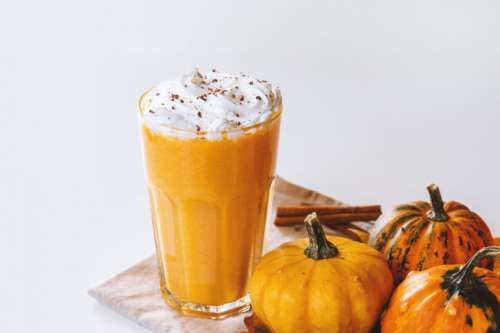 Pumpkin smoothie. Small pumpkins and drink on the white background