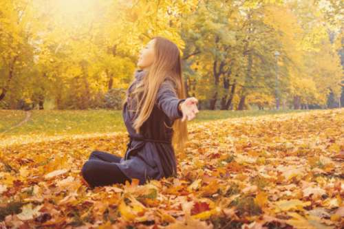 Young woman sitting on a fallen autumn leaves in a park