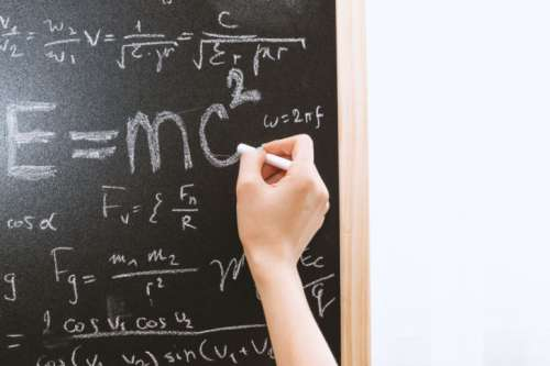 Female hand holding white chalk in front of a blackboard with Einstein formula. Education and school concept.