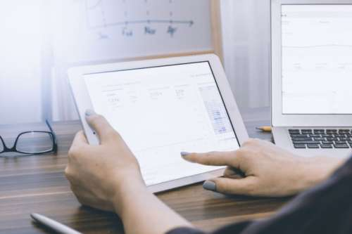 Business person analyzing Google Analytics on tablet