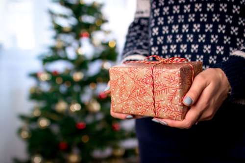 Woman's hands hold christmas gift box. Merry Christmas