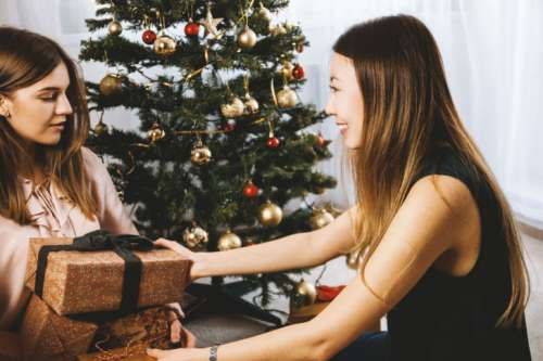 Young girl is giving her beautiful young friend a present. Merry Christmas