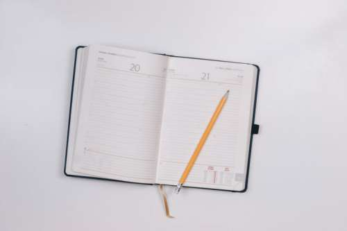 Diary on white table with a pencil