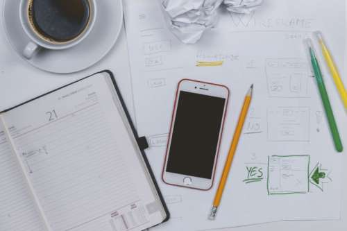 Web developer make some prototyping. Coffee, diary and smartphone on the table