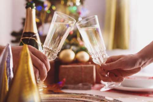 Female and male hands toasting with glasses of champagne