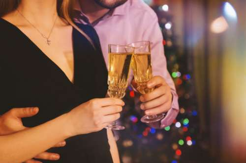 Man hugging his woman while they celebrate with champagne in hands at home