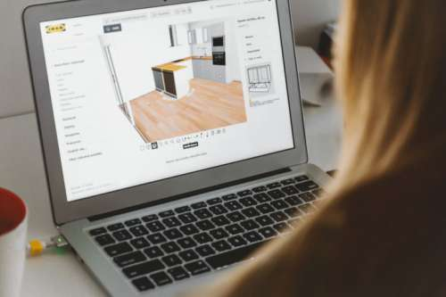 Woman uses 3D planning software for her new kitchen on laptop at home