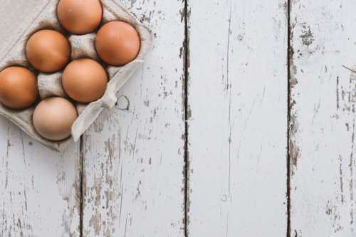 Close-up view of chicken eggs in egg box on white wooden background