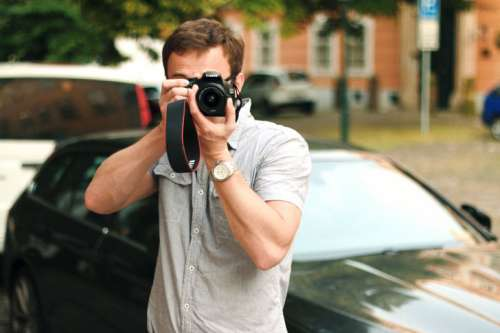 Photographer with a DSLR camera in hand on the street
