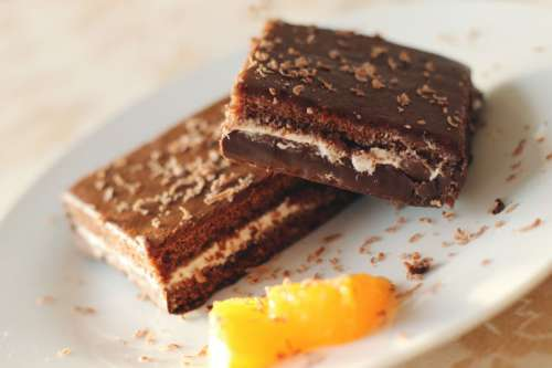 Two pieces of chocolate dessert with orange