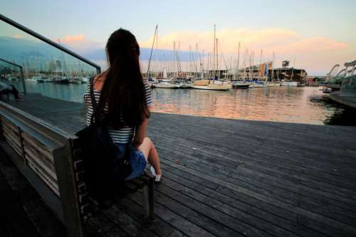 Girl behind watching the sunset over the harbor