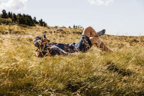 Happy man lying on green grass meadow in mountains enjoying the sun