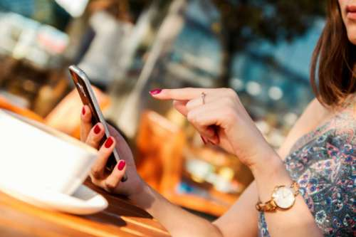 Young girl typing message on her smartphone in the restaurant garden
