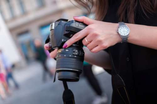 Young photographer checks the her DSLR camera in the city center