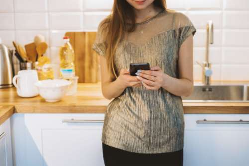 Woman texting with smart phone in kitchen