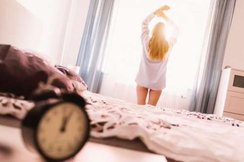 Girl wake up on Cozy bedroom at noon