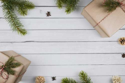Christmas composition. Christmas gifts, branches of a Christmas tree on wooden white background.