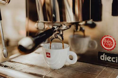 Close-up of coffee pouring from coffee machine into white cup at restaurant