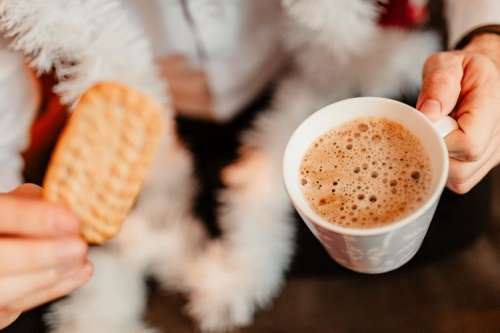 Drinking coffee with milk and cookies in a holiday mood