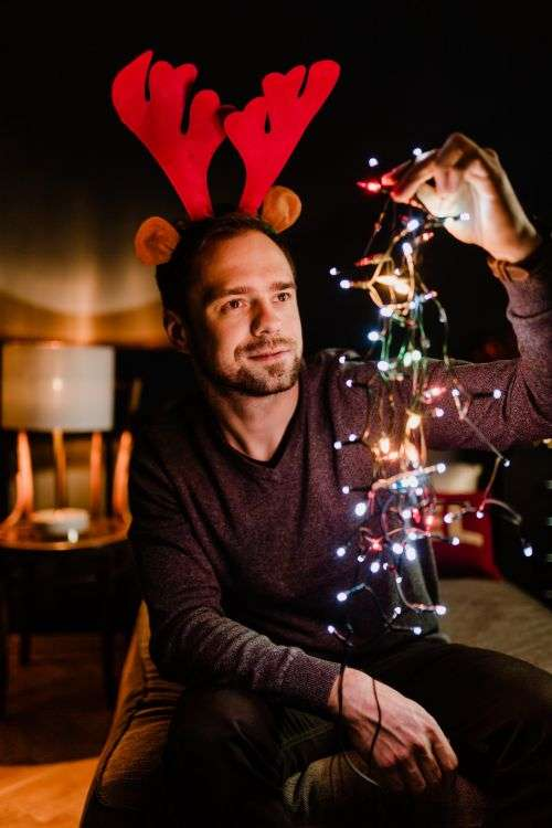 A handsome young man with Christmas tree lights