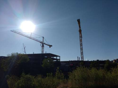 Blue Sky with Construction Cranes and Sun