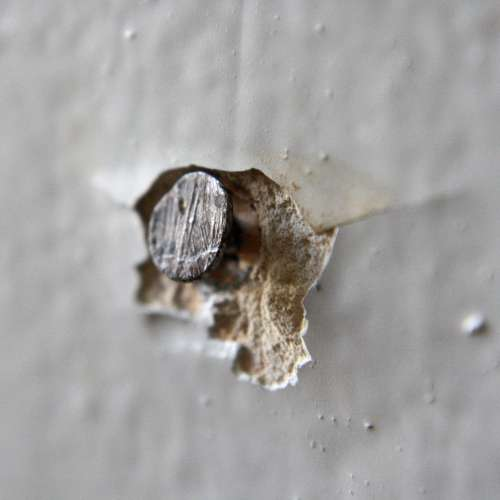 Nail Head Sticking out of Wall